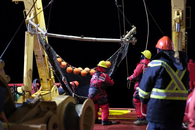 People operating large nets on the deck of a ship at night
