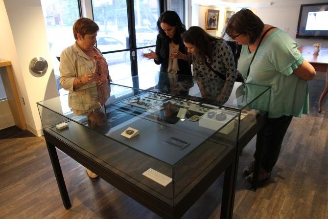 4 people viewing items in a glass display