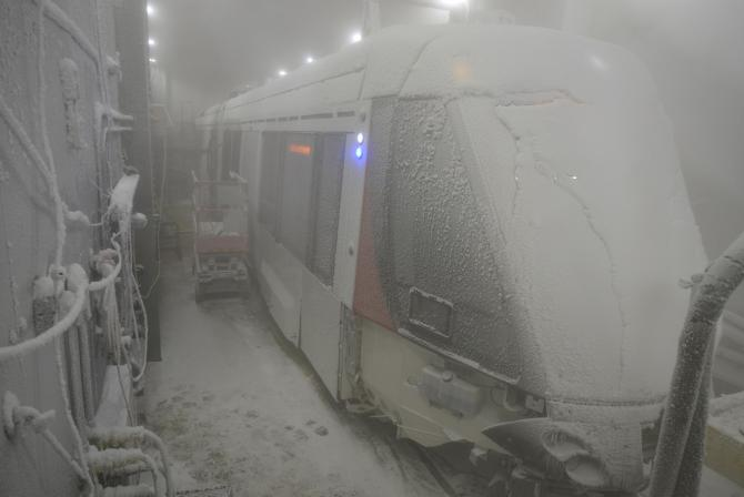 Passenger rail vehicle covered in ice/snow in large chamber