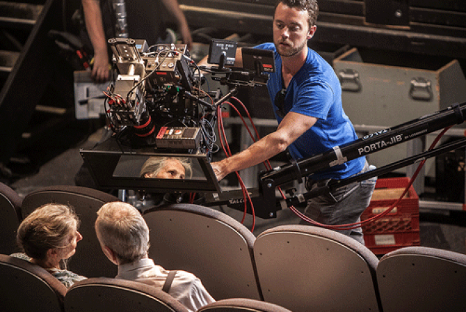 Camera operator films a couple seated in theatre seats