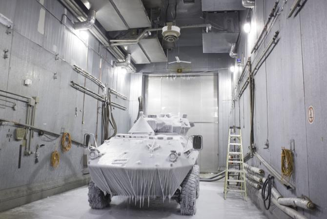 Military vehicle covered in ice in large chamber