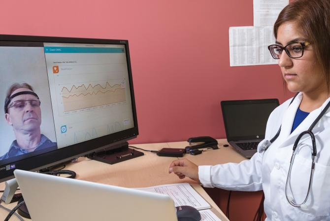 Researcher testing interactive software displaying remote patient data
