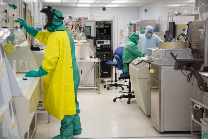 Three researchers dressed in full-body hazmat suits use research infrastructure in a lab
