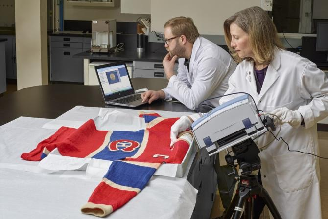 Two scientists use research infrastructure to perform analysis on a Montreal Canadiens hockey jersey