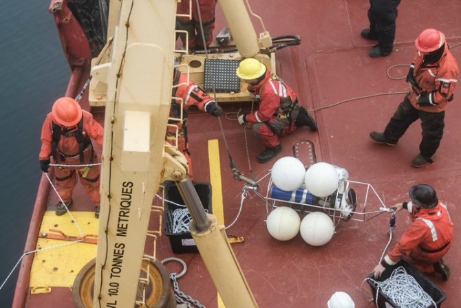 Group of people working with various pieces of equipment on the deck of a boat