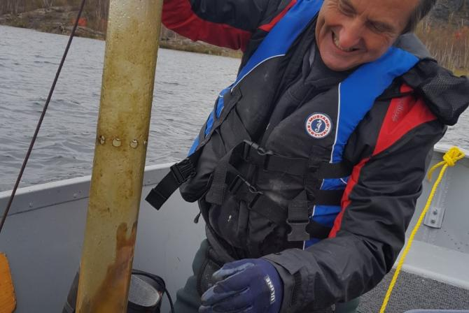 Researcher uses a suspended sediment trap on a boat