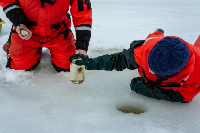 Researchers in the field gather water from a hole drilled in the ice