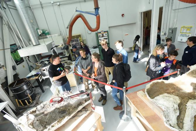 Photo taken from above of about ten people looking at fossils on tables behind guide ropes in a lab setting