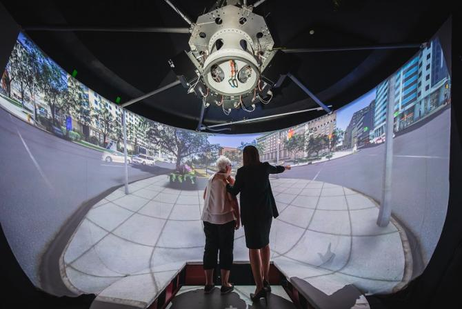 Two people stand in the middle of a curved screen displaying a city street