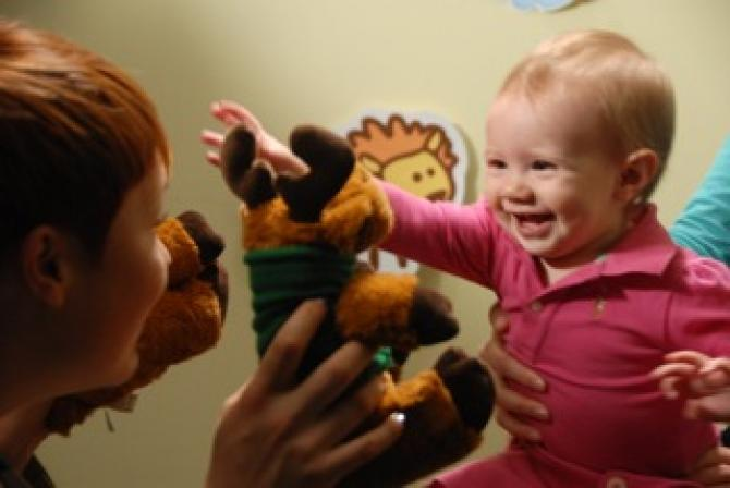 Person plays with stuffed animals in front of a smiling infant