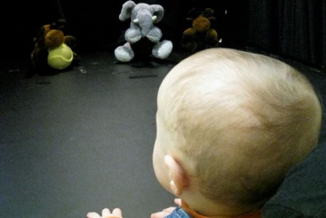 An infant sits in front of stuffed animals