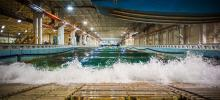 Wave crashing up against the side of a large rectangular indoor water tank