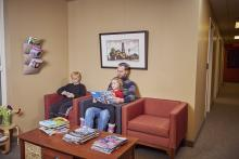 Man and 2 children sit in a waiting room
