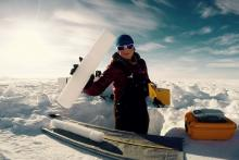 Researcher surrounded by snow holds an ice core