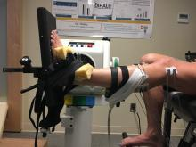 Leg device set-up where subject sits in a chair with electrodes and measurement devices attached the raised left leg and foot