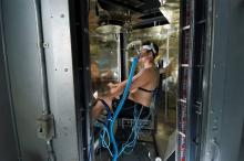 Person seated in a chamber is covered with measurement devices and sensors