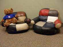 2 colourful children's stuffed chairs and teddy bear
