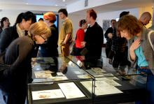 People view drawings and images displayed in glass cases